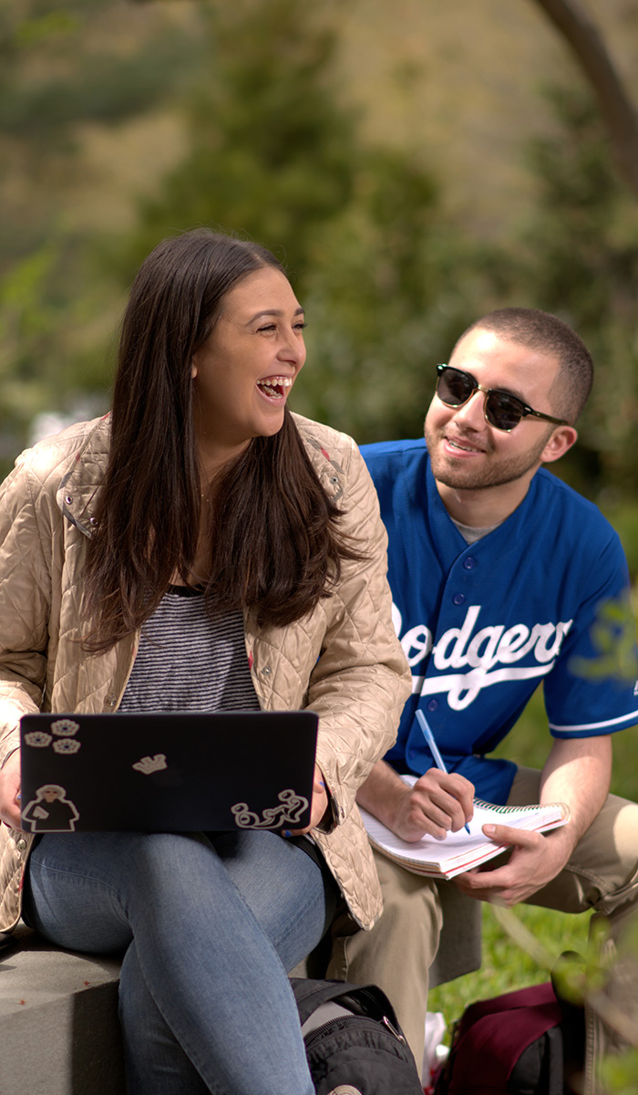 Female student with a laptop laughing with a male friend