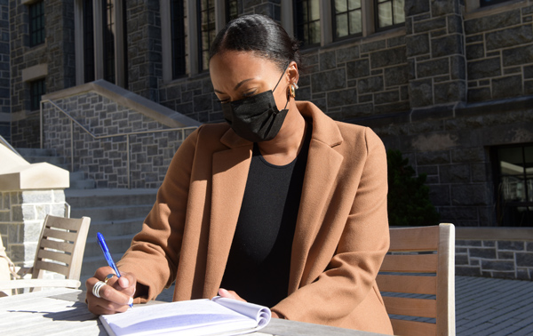 Catholic U student seated at outdoor table writing in notebook