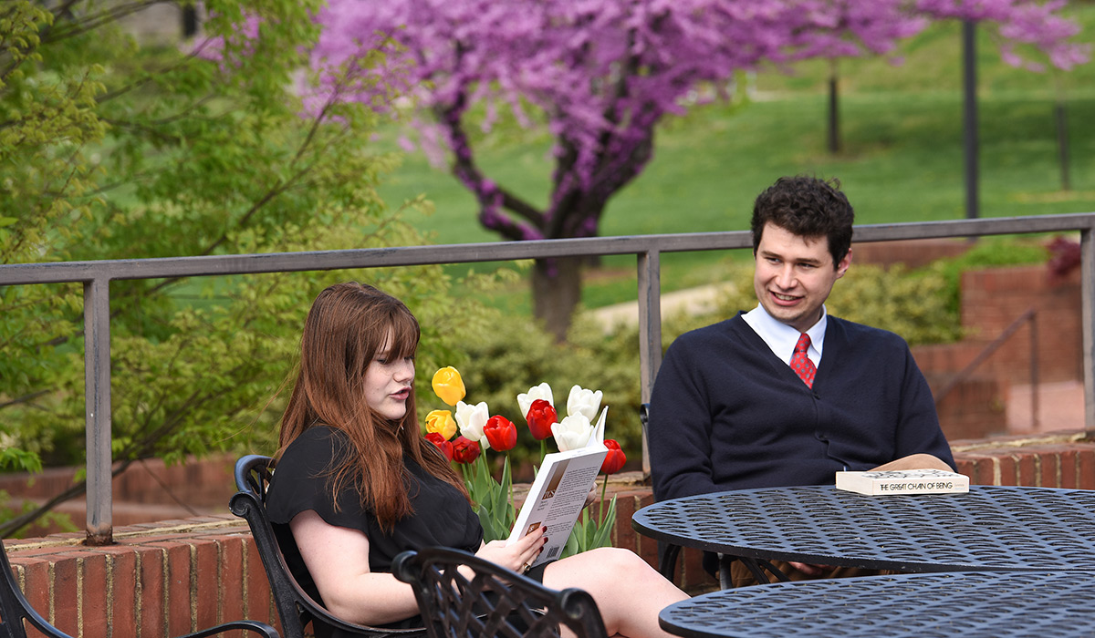 Students sitting outside reading philosophy books