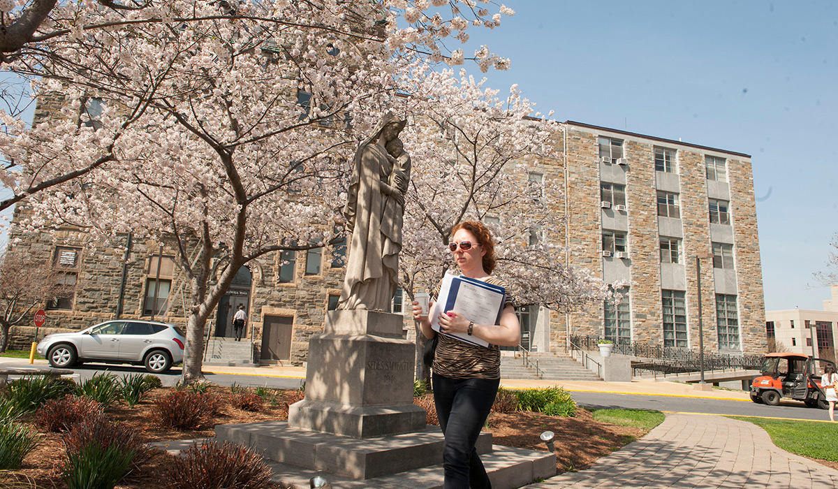 Student walking with books in front of statue of Mary