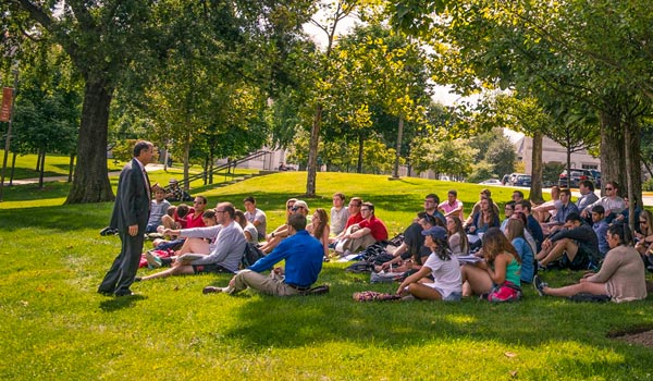 Students sitting on grass listening to an outdoor lecture