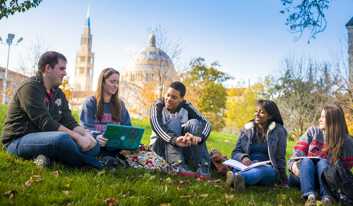 Students meeting on a lawn.