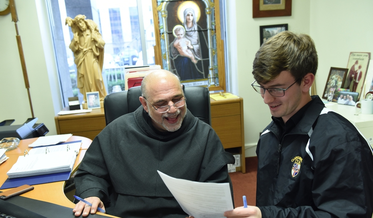 Father Jude, campus chaplain, speaking to a male student