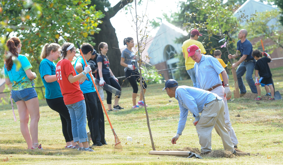 President Garvey and students planting a tree
