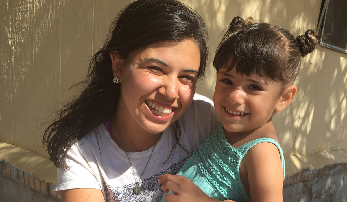 Junior Marissa Coene hugs a child she met while painting homes in New Mexico colonias.