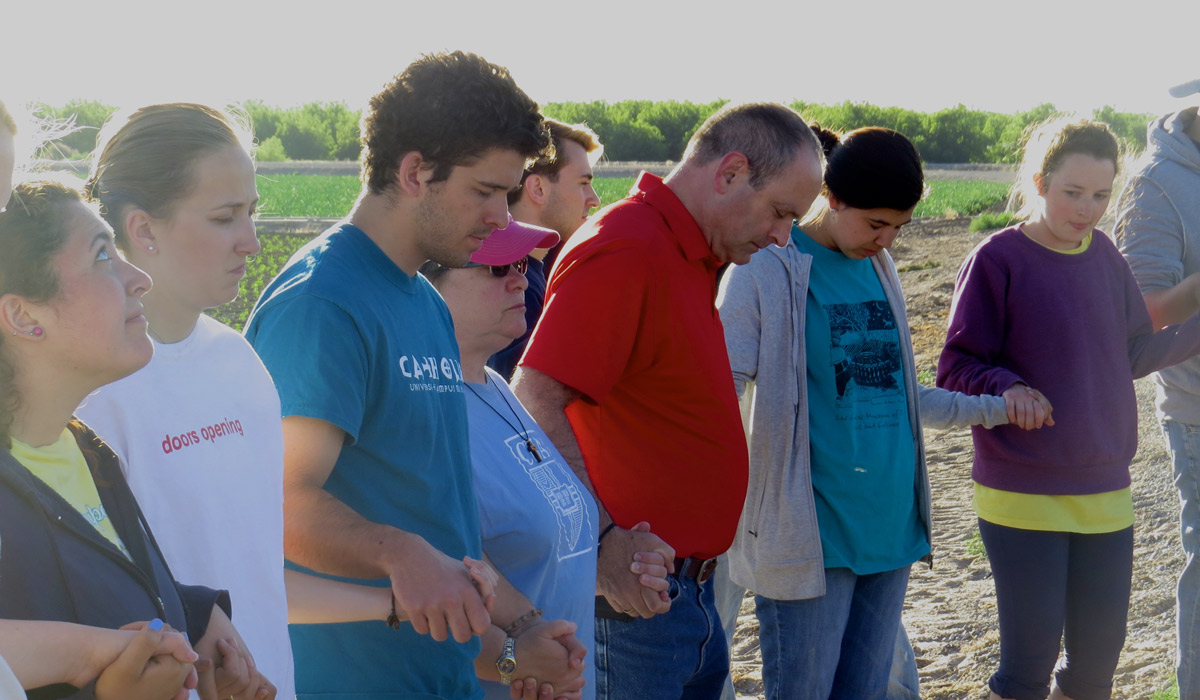 Catholic University students pray during Mass at a chile farm in Hatch, New Mexico.