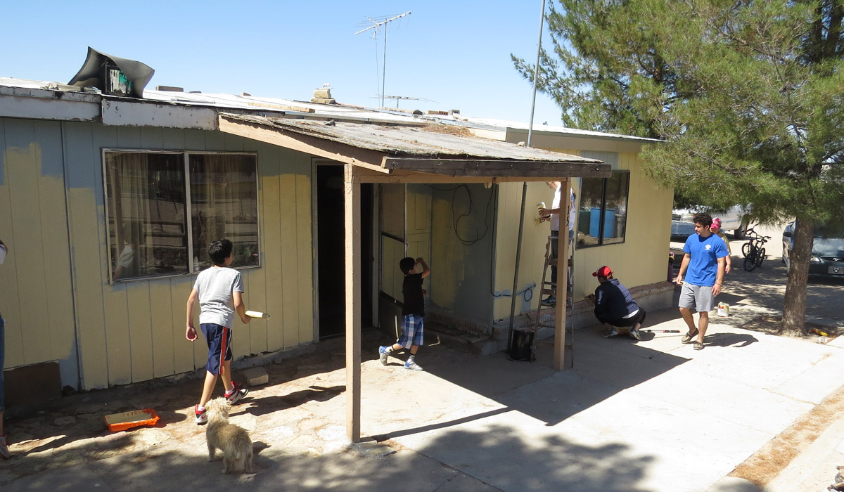 Children play as Catholic University students paint their home in Anthony, N.M.