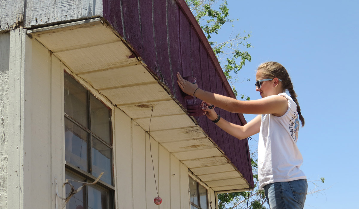 Sophomore Anne Riley paints the garage of a home belonging to an undocumented family in Anthony, N.M.