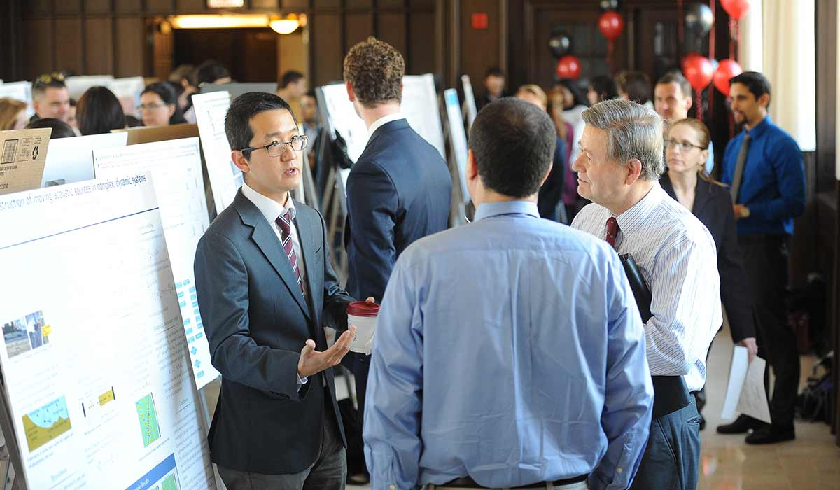 A student researcher explains his research to members of the University faculty, including James Greene, dean of graduate studies (right).