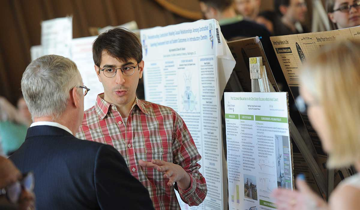 Architecture student Majd Hijazi explains his research project to Herbert Hartmann, clinical assistant professor of philosophy.