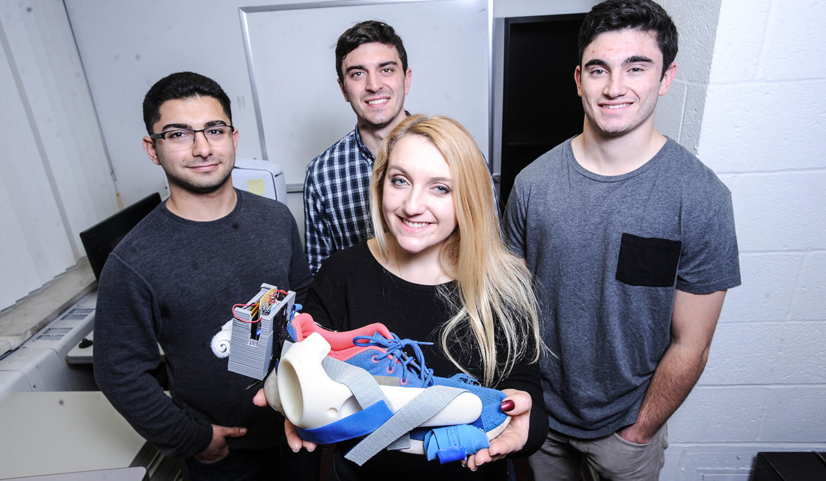Senior Ben Pesante (second from left) and his research group (from left) Sean Adams, Christine Dedoulis, and Ben Rahimi, display their biomedical engineering senior design project, a shoe that measures foot motion. The group has been testing their project at the National Institute of Health in Bethesda, Md