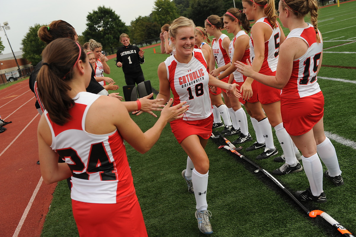 Girls field hockey team high fives each other in preparation for a game