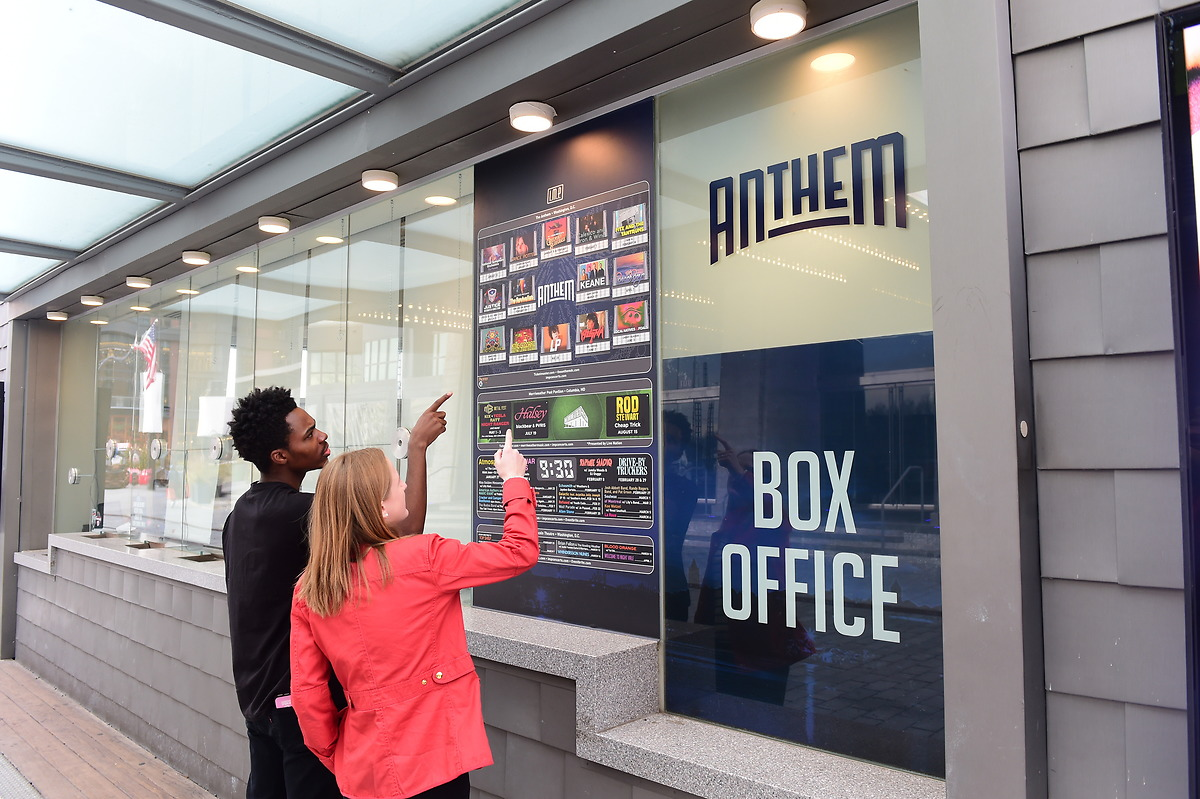 Students look at showtimes and tickets at a box office at The Wharf in DC.