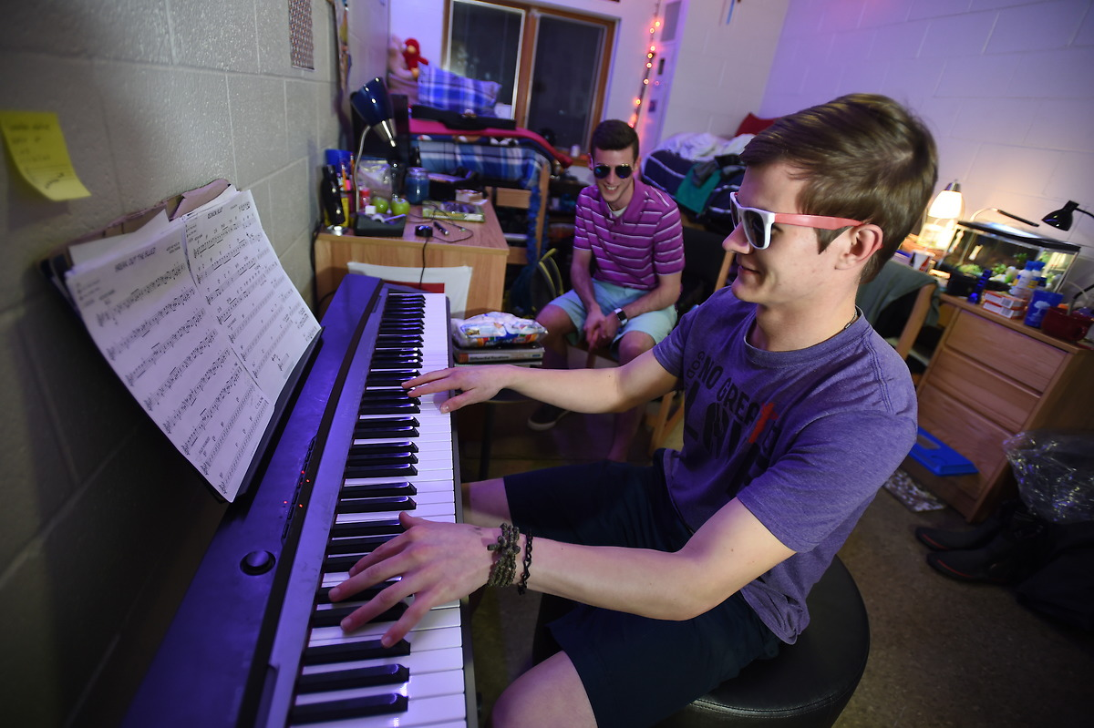 Boys play the keyboard in their residence hall room.