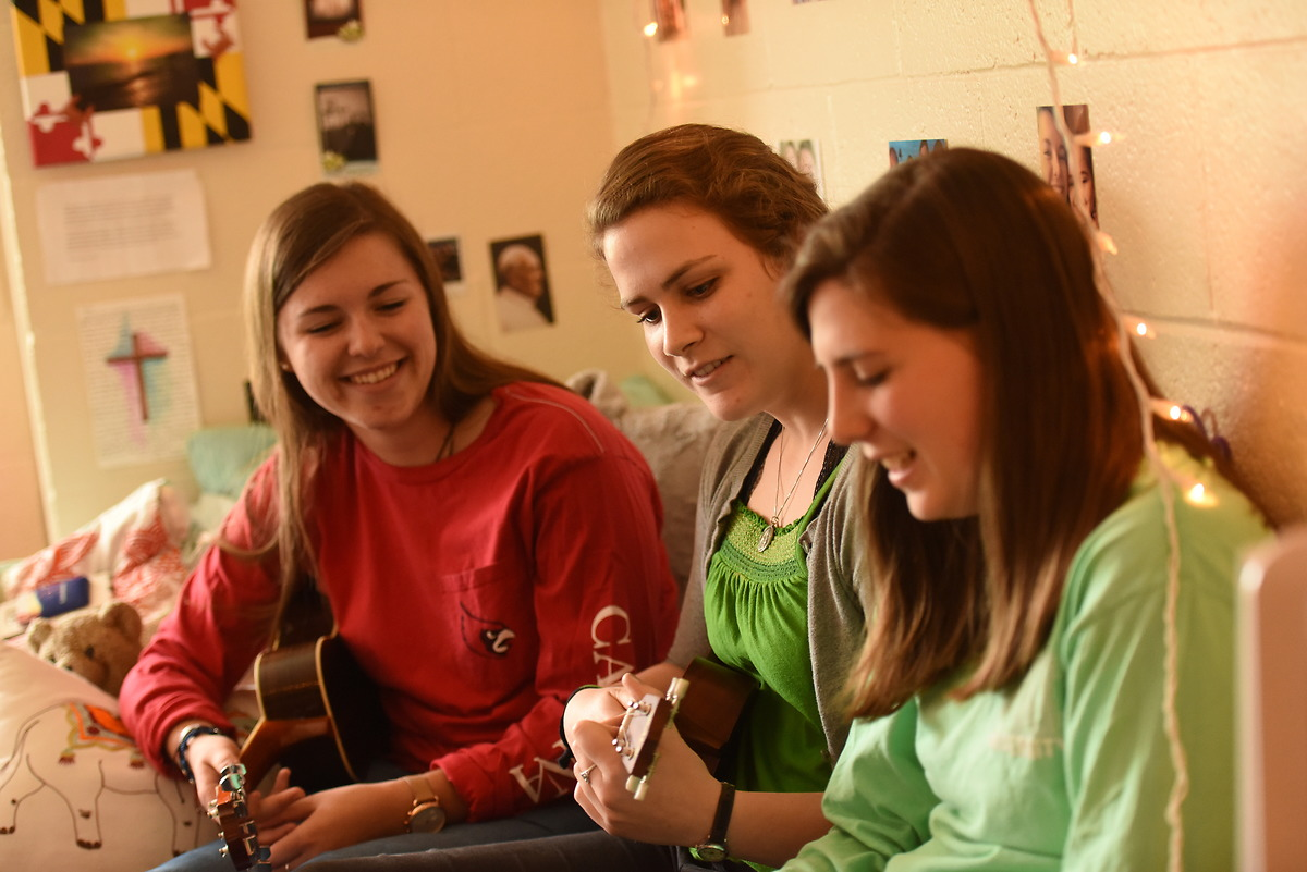 Girls play the ukelele in their residence hall room.