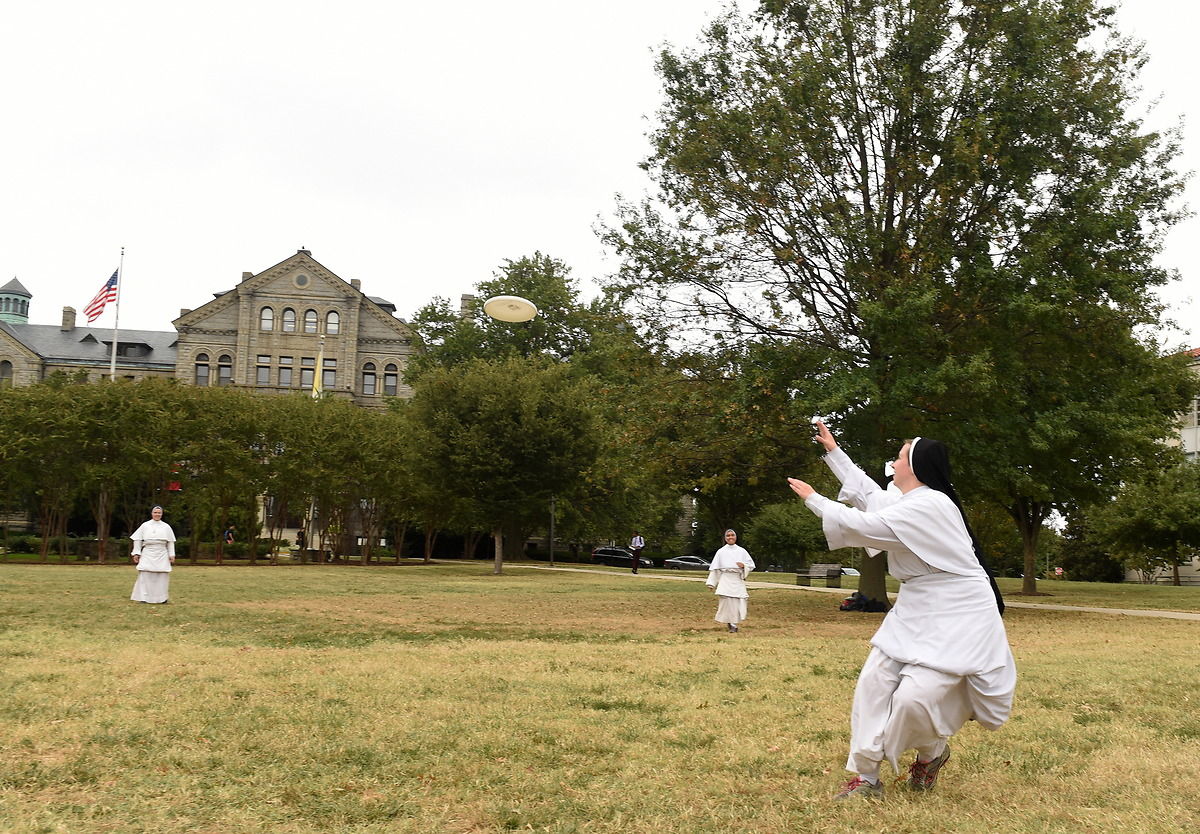Dominican Sisters play frisbee on the Basilica lawn in full habit.
