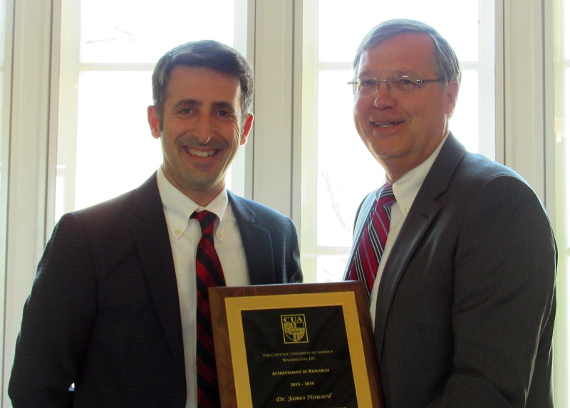 Provost Andrew Abela and Marc Sebrechts, chair of the Department of Psychology, pose with the Outstanding Achievement in Research and Scholarship award that Sebrechts accepted on behalf of James Howard Jr