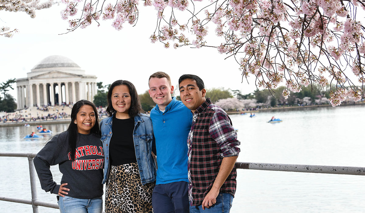 Students standing in front of cherry blossoms with Jefferson Memorial in background