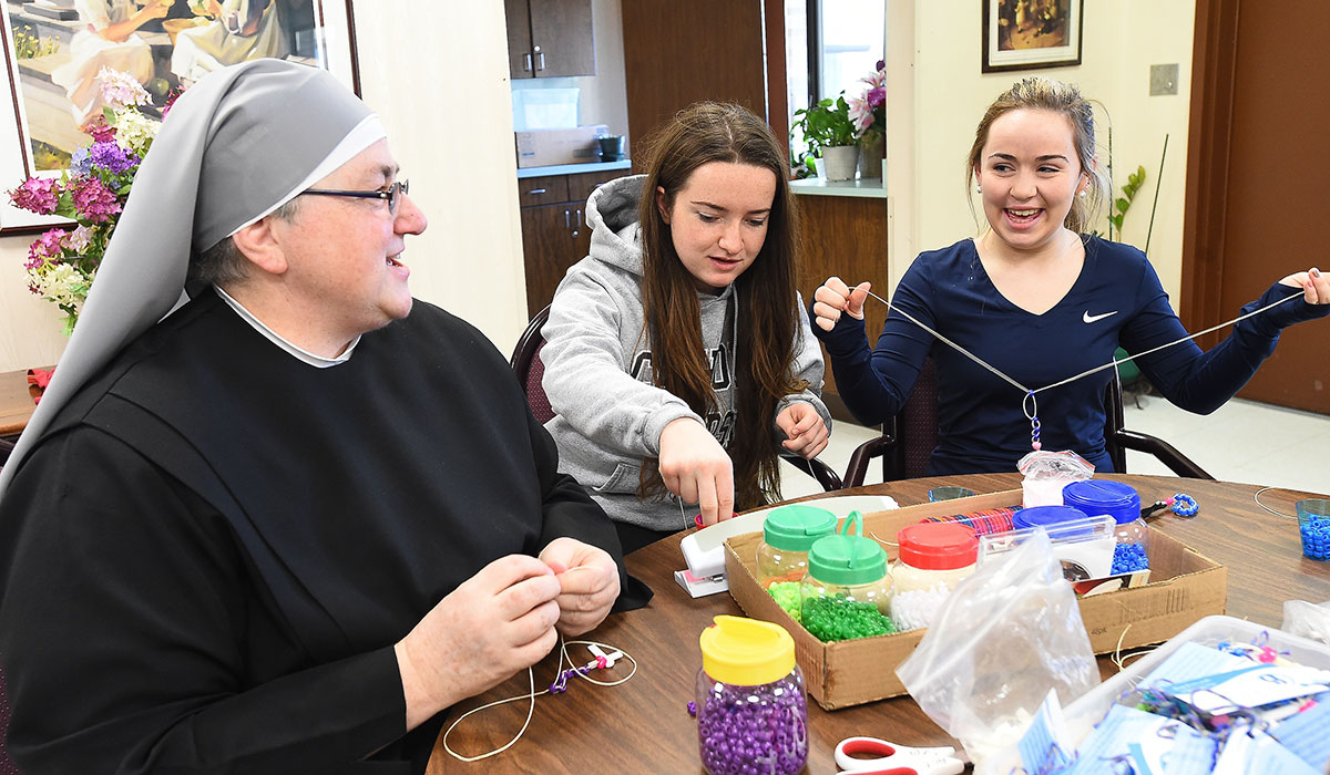 Students doing crafts with nun