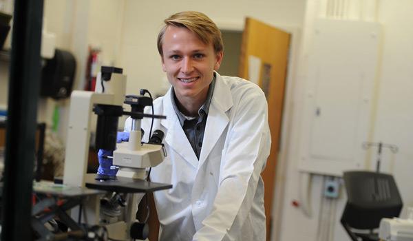 Male biomedical engineering student behind equipment