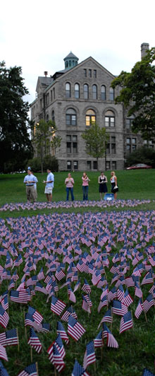 Students place flags on the lawn next to McMahon Hall to commemorate those who lost their lives during the 9/11 terrorist attack.